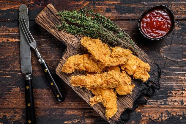 Paski kurczaka na drewnianej desce do krojenia