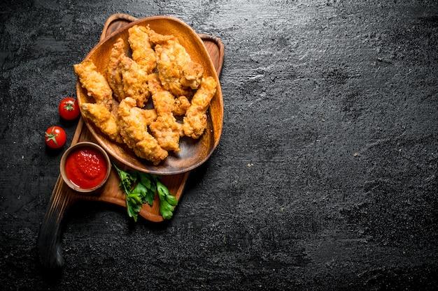 Paski kurczaka na talerzu z pietruszką i sosem na czarnym rustykalnym stole.