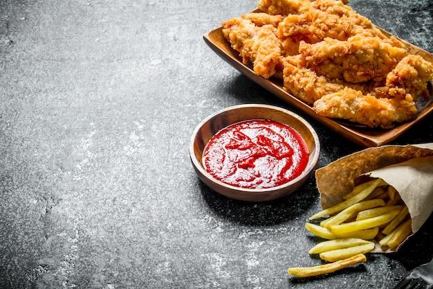 Paski kurczaka z frytkami i sosem na ciemnym rustykalnym stole