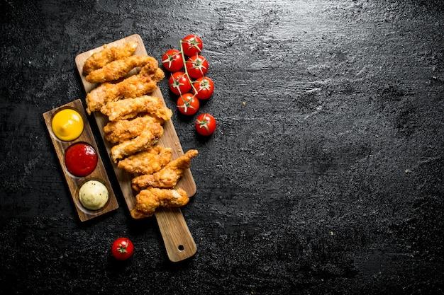Paski kurczaka z pomidorkami koktajlowymi i różnymi sosami na czarnym rustykalnym stole.