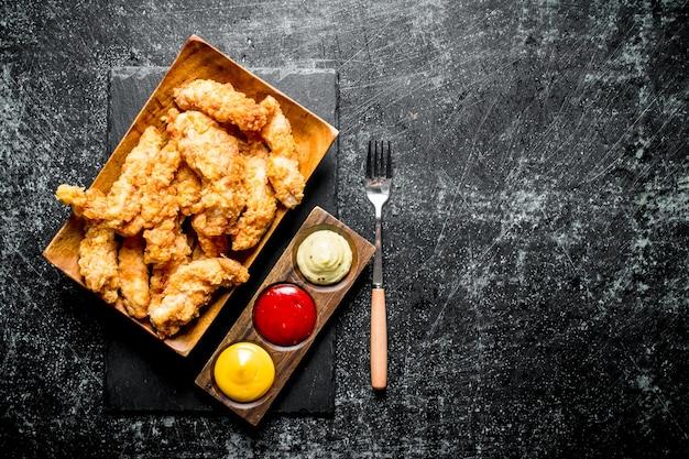 Paski kurczaka z różnymi sosami i widelcem na czarnym rustykalnym stole.