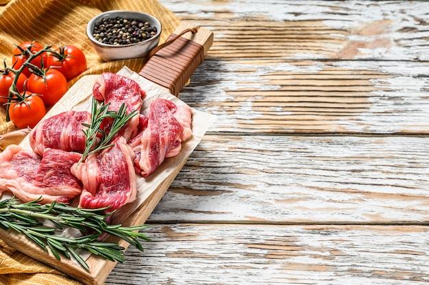 Paski marmurkowej wołowiny, szybki stek na desce do krojenia. białe tło drewniane. widok z góry. skopiuj miejsce.