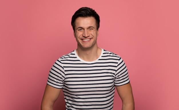 Paski. szczęśliwy młody człowiek w t-shirt w paski, który uśmiecha się, patrząc w kamerę.