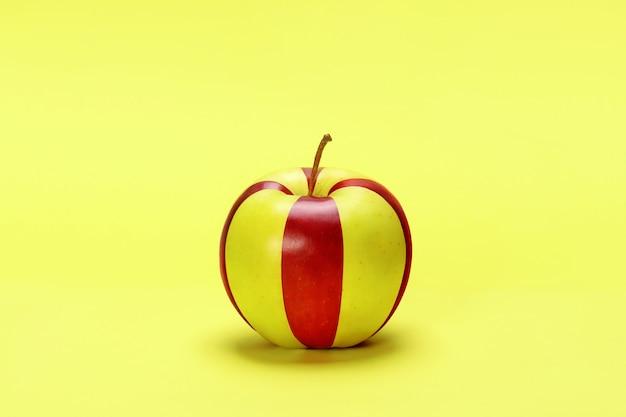 Paski żółte i czerwone jabłko na żółtym tle.