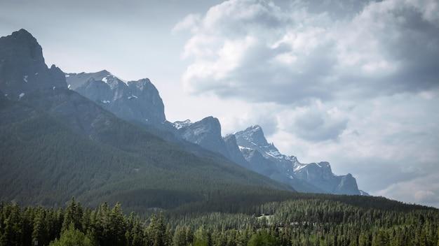 Pasmo górskie z podpuchniętymi chmurami nad nim, krajobraz wykonany w canmore, alberta, kanada
