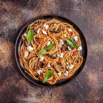 Pasta alla norma - tradycyjne włoskie jedzenie z bakłażanem, pomidorem, serem i bazylią