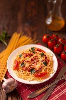 Pasta carbonara z sosem pomidorowym i mielonym mięsem, tartym parmezanem i świeżą pietruszką