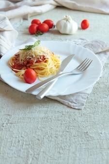 Pasta fettuccine bolognese z sosem pomidorowym na białym talerzu. carlic, sól i pomidory na betonowym tle z lnianymi serwetkami.
