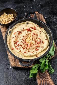 Pasta hummusowa z ciecierzycą i natką pietruszki w misce.