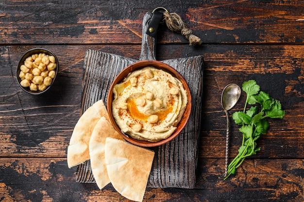 Pasta hummusowa z pitą, ciecierzycą i natką pietruszki w drewnianej misce.