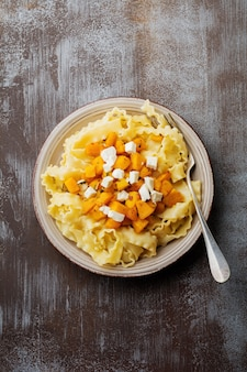 Pasta mafaldine napoletane z pieczoną dynią, serem feta i przyprawami na talerzu ceramicznym. styl rustykalny. widok z góry.