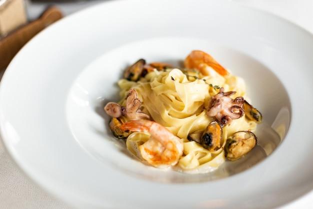 Pasta z owoców morza: małże, krewetki i ośmiornice w kremowym sosie, podawane na białym talerzu na stole z białym obrusem, instrumentami i lampką wina w restauracji