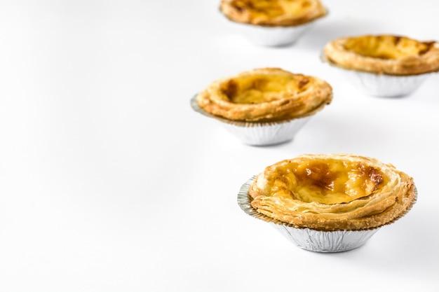 """""""pasteis de nata"""". typowy portugalski tarta z kremem jajecznym na białym tle na białej powierzchni"""