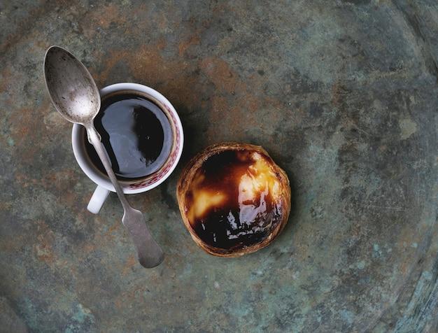 Pastel de nata. tradycyjna portugalska tarta jajko deserowe i filiżankę kawy na rustykalnym tle metalowe. widok z góry