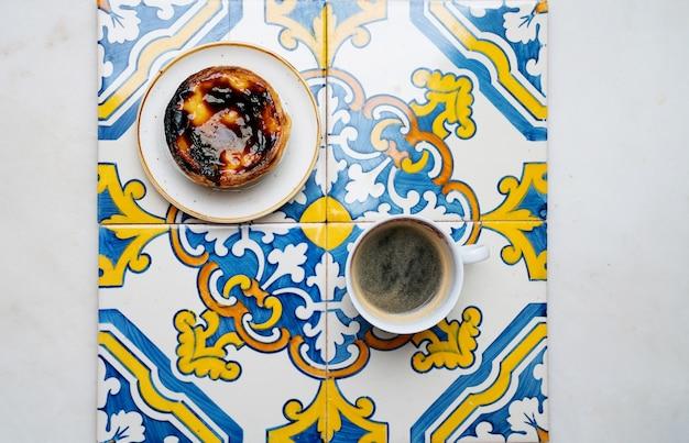 Pastel de nata. tradycyjny portugalski deser, tarta jajeczna i filiżanka kawy nad tradycyjnymi kafelkami azulejo. widok z góry