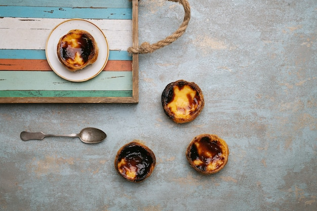 Pastel de nata. tradycyjny portugalski deser, tarta jajeczna na drewnianej tacy na rustykalnym tle. widok z góry