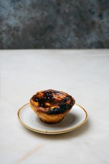 Pastel de nata. tradycyjny portugalski deser, tarta jajeczna na marmurowym tle przed rustykalnym metalowym tłem. selektywna ostrość