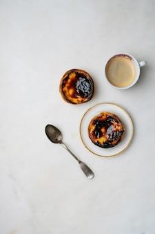 Pastel de nata. tradycyjny portugalski deser, tarta jajeczna na talerzu ceramicznym i dookoła z filiżanką kawy i łyżeczką na marmurowym tle. widok z góry