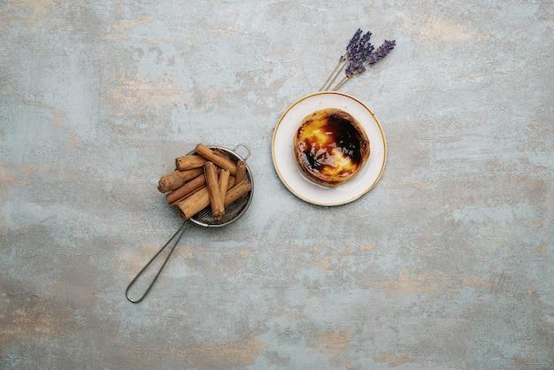 Pastel de nata. tradycyjny portugalski deser, tarta jajeczna na talerzu na rustykalnym tle z laskami cynamonu w sitku i suszonymi gałązkami lawendy. widok z góry