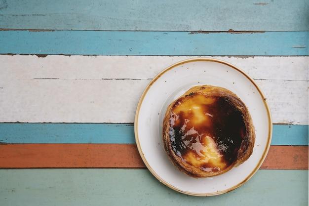 Pastel de nata. tradycyjny portugalski deser, tarta jajeczna na talerzu nad drewnianą tacą. widok z góry