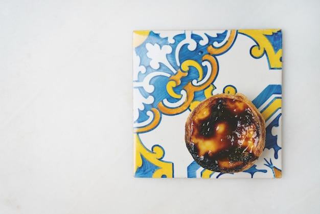 Pastel de nata. tradycyjny portugalski deser, tarta jajeczna na tradycyjnych kafelkach azulejo na marmurowym tle. widok z góry