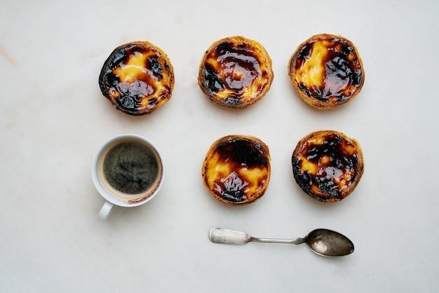 Pastel de nata. tradycyjny portugalski deser, tarta jajeczna z filiżanką kawy na tle marmuru. widok z góry