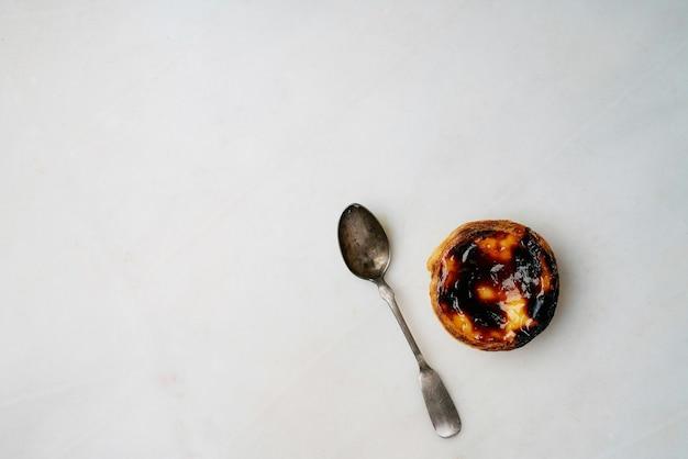 Pastel de nata. tradycyjny portugalski deser, tarta jajeczna z łyżeczką na marmurowym tle. widok z góry