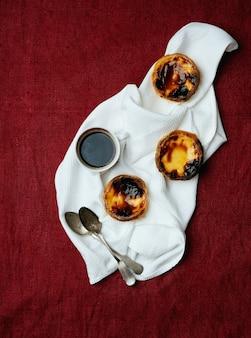 Pastel de nata. tradycyjny portugalski deser, tarty jajeczne i filiżankę kawy na serwetce na tle włókienniczych. widok z góry
