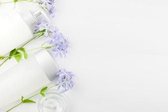 Pastelowa kompozycja kosmetyków i kwiatów