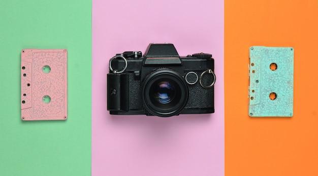 Pastelowa taśma retro w kasecie audio i kamera filmowa na kolorowym tle papieru. skopiuj miejsce minimalistyczny trend.