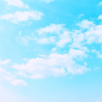 Pastelowe błękitne niebo z białymi chmurami - tło z miejscem na własny tekst