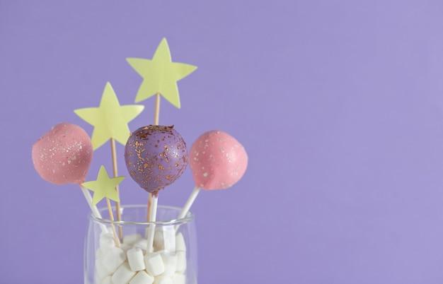 Pastelowe kolorowe ciasto wyskakuje w szklance na fioletowej ścianie. koncepcja na urodziny, wakacje. obraz poziomy. kopia przestrzeń.