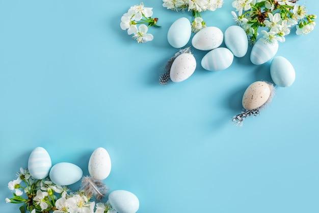 Pastelowe kolorowe pisanki i wiosenne kwitnące gałęzie na niebiesko.