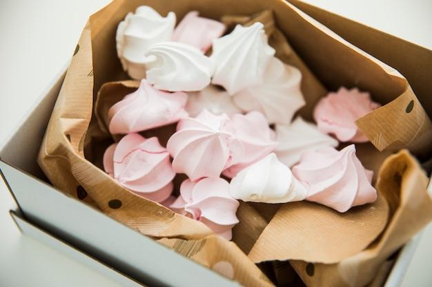 Pastelowe kolorowe zefiry owinięte w papier wewnątrz otwartego pudełka