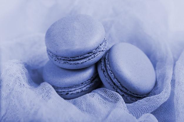 Pastelowe miękkie ciasta macaron lub makaronik na zwiewnej tkaninie