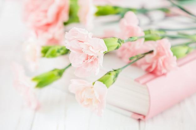 Pastelowe różowe goździki na książce