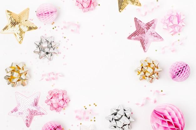 Pastelowe różowe konfetti, kokardki i papierowe dekoracje. płaski świeckich, widok z góry. wakacyjna kompozycja na przyjęcie urodzinowe, obchody nowego roku/boże narodzenie lub temat koncepcji wieczoru panieńskiego. płaski układanie, widok z góry