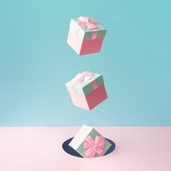 Pastelowe różowe pudełka na prezenty świąteczne na niebieskim i różowym tle.