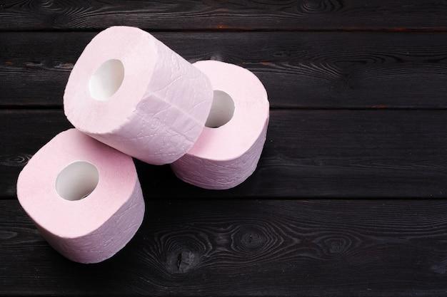Pastelowe różowe rolki papieru toaletowego na czarnym drewnianym stole