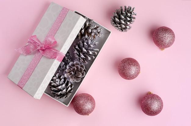 Pastelowe różowe święta. otwierane pudełko upominkowe wypełnione srebrnymi stożkami i bombkami.