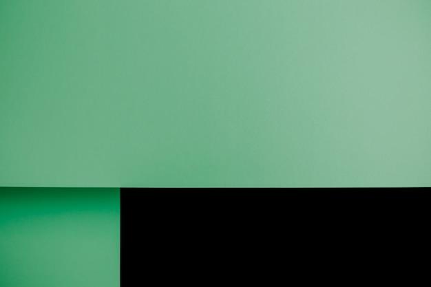 Pastelowe zielone i czarne płaskie tło z ostrymi warstwami i cieniami z miejscem na kopię