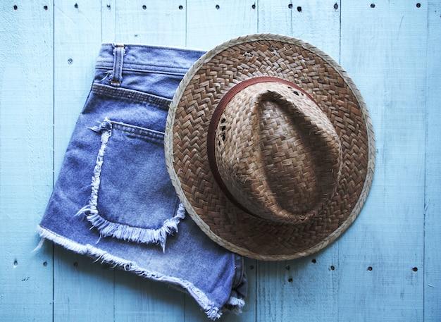 Pastelowy kolor, styl vintage, kapelusz, dżinsy na tle drewna.
