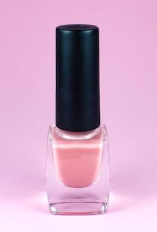 Pastelowy lakier do paznokci na różowym tle. makijaż, kosmetyki, uroda. zbliżenie, makro.