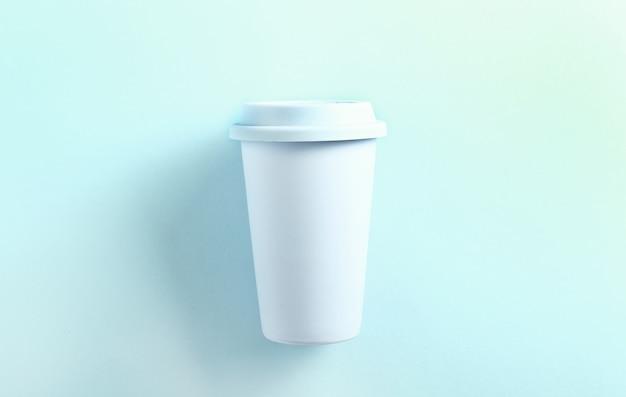 Pastelowy niebieski ceramiczny kubek podróżny na niebiesko. widok z góry, leżał płasko. kubek tumbler na niebiesko.