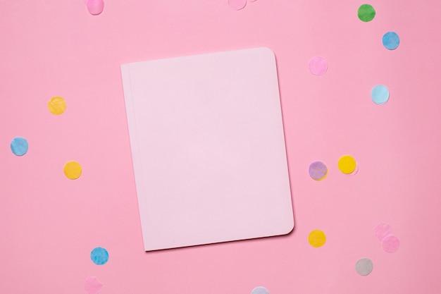 Pastelowy notes papierowy na różowym tle z kolorowym konfetti