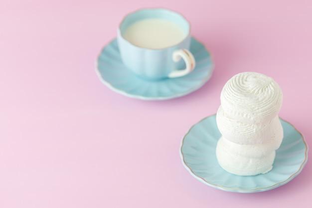 Pastelowy różowy poziomy baner z białym zefir na niebieski talerz i kubek mleka.