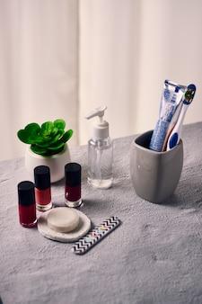 Pasty do paznokci, mydło, szczoteczka do zębów, pilnik do paznokci, gąbka, butelka środka dezynfekującego i roślinka