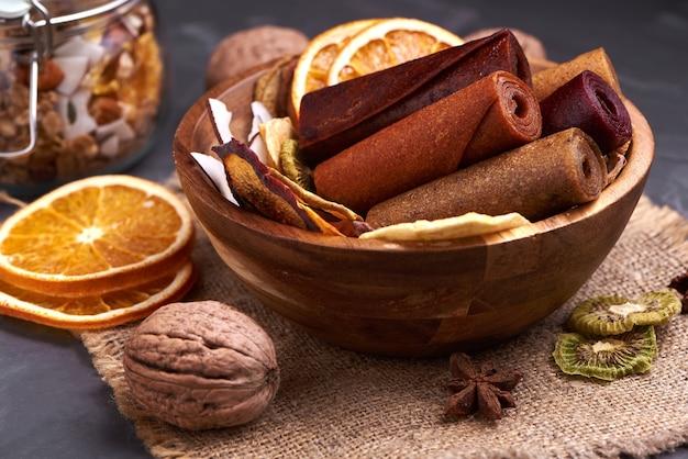 Pastylka owocowa i suszone owoce w drewnianym kubku