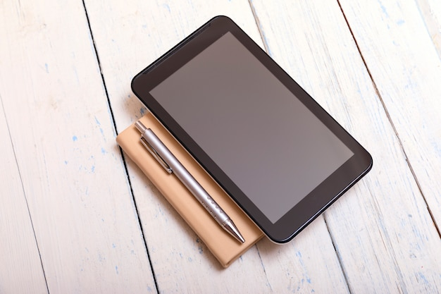 Pastylka z notatnikiem na białym drewnianym stole i piórze shabbi