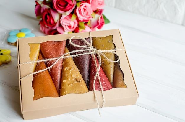Pastylki owocowe ze skóry owocowej w pudełku z bukietem róż na stole